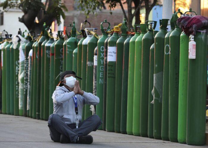 Alejandro Ccasa reza tras pasar tres días esperando junto a un tanque de oxígeno vacío para su tío, que tiene COVID-19, en el exterior del establecimiento donde es el primero en la fila para rellenarlo, en Callao, Perú, el 2 de febrero de 2021. El tío de Ccasa falleció más tarde en el día. (AP Foto/Martín Mejía)