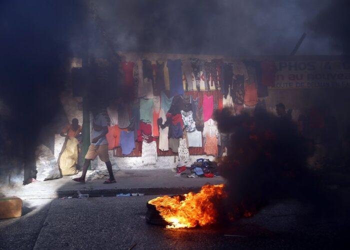 El humo de neumáticos quemados por manifestantes cubre una calle en Delmas, donde vendedores callejeros venden ropa durante una huelga nacional para exigir la renuncia del presidente, Jovenel Moise, en Puerto Príncipe, Haití, el 1 de febrero de 2021. (AP Foto/Dieu Nalio Chery)