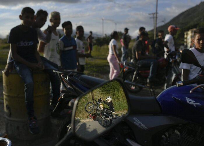 Reflejado en el espejo retrovisor de una moto, Pedro Aldana pone su moto en equilibrio sobre una sola rueda durante una exhibición en el vecindario de Ojo de Agua, en Caracas, Venezuela. La imagen fue tomada el 10 de enero de 2021 y publicada el 1 de febrero. (AP Foto/Matías Delacroix)