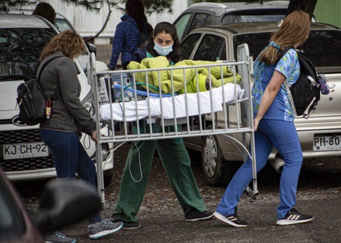 Trabajadoras sanitarias evacuan a un menor durante un incendio en el hospital de San Borja Arrarián, en Santiago, Chile, el 30 de enero de 2021. (AP Foto/Esteban Félix)